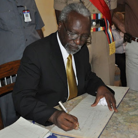 the 3rd Deputy Prime Minister/Minister of Internal Affairs Hon. A.M. Kirunda Kivejinja signs the act in 2011